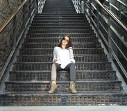 Femme assez élégante de jeunes s'asseyant sur des escaliers Images libres de droits