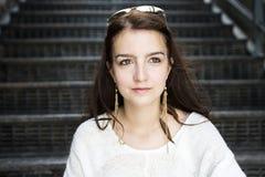Femme assez élégante de jeunes s'asseyant sur des escaliers Photographie stock libre de droits