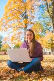 Femme assez amicale s'asseyant en parc d'automne Photographie stock