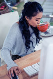Femme assez asiatique à l'aide de l'ordinateur et buvant par la tasse Image libre de droits