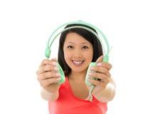 Femme assez asiatique écoutant des écouteurs de musique image stock
