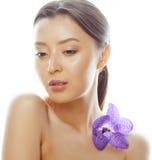 Femme assez asiatique de jeunes avec la fin pourpre d'orchidée de fleur d'isolement sur la station thermale blanche de fond, conc Image stock