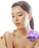 Femme assez asiatique de jeunes avec la fin pourpre d'orchidée de fleur d'isolement sur la station thermale blanche de fond, conc Photo stock