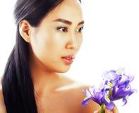 Femme assez asiatique de jeunes avec la fin pourpre d'orchidée de fleur d'isolement sur la station thermale blanche de fond, conc Photographie stock