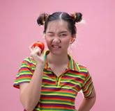 Femme assez asiatique de jeunes tenant une tomate mûre photo stock