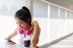 Femme assez asiatique de portrait : La fille attirante regarde le smartphone photographie stock