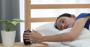 Femme assez asiatique refusant de réveiller le mensonge sur son lit banque de vidéos