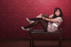 Femme assez asiatique s'asseyant dans l'intérieur de luxe de chambre Image libre de droits
