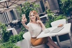 Femme assez attirante faisant l'autoportrait au téléphone intelligent pour images stock