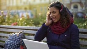 Femme assez aux cheveux ondulés chantant la chanson préférée tout en écoutant la musique dehors Image libre de droits