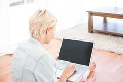 Femme assez blonde à l'aide de son ordinateur portable sur le plancher photographie stock libre de droits