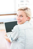 Femme assez blonde à l'aide de son ordinateur portable sur le plancher Images stock