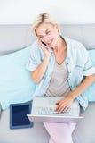 Femme assez blonde à l'aide de son ordinateur portable tout en invitant le téléphone photos libres de droits