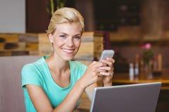 Femme assez blonde à l'aide de son smartphone Photographie stock libre de droits