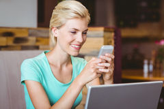 Femme assez blonde à l'aide de son smartphone Photographie stock