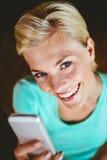 Femme assez blonde à l'aide de son smartphone Image stock