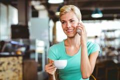 Femme assez blonde à l'aide de son smartphone avec une tasse de café Image libre de droits