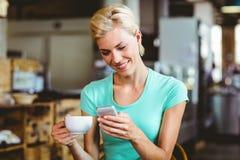 Femme assez blonde à l'aide de son smartphone avec une tasse de café Photos libres de droits