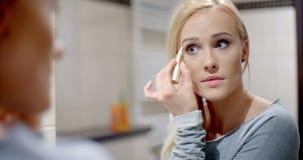 Femme assez blonde appliquant le maquillage de sourcil banque de vidéos