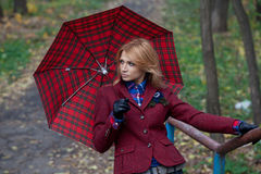 Femme assez blonde avec le parapluie dans des mains posant sur le pont Image stock