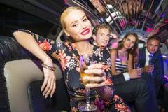 Femme assez blonde dans une limousine entourée par des amis Images stock