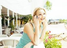 Femme assez blonde de jeunes après se reposer de achat au café dehors sur parler heureux de sourire de rue au téléphone, mode de  Image libre de droits