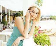 Femme assez blonde de jeunes après se reposer de achat au café dehors sur parler heureux de sourire de rue au téléphone, mode de  Photographie stock libre de droits
