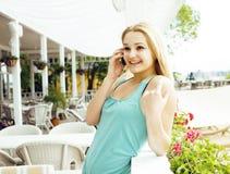 Femme assez blonde de jeunes après se reposer de achat au café dehors sur parler heureux de sourire de rue au téléphone, mode de  Images libres de droits