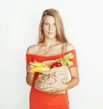 Femme assez blonde de jeunes aux achats avec la nourriture dans le sac de papier d'isolement sur le sourire de blanc lumineux, co Photo libre de droits