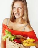 Femme assez blonde de jeunes aux achats avec la nourriture dans le sac de papier d'isolement sur le sourire de blanc lumineux, co Photos stock