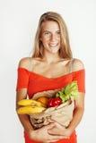 Femme assez blonde de jeunes aux achats avec la nourriture dans le sac de papier d'isolement sur le sourire de blanc lumineux, co Photo stock