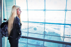 Femme assez blonde de jeunes regardant dans l'aéroport de fenêtre Image libre de droits