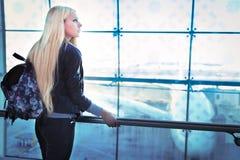 Femme assez blonde de jeunes regardant dans l'aéroport de fenêtre Photo stock