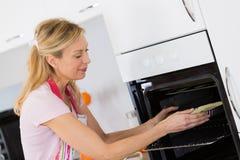 Femme assez blonde mettant la tarte en four pour la cuisson photographie stock libre de droits