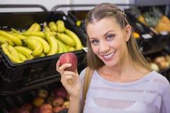 Femme assez blonde montrant une pomme rouge Photos libres de droits