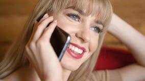 Femme assez blonde parlant au téléphone à la maison Images libres de droits