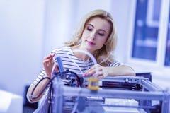 Femme assez blonde regardant attentivement des détails photographie stock libre de droits