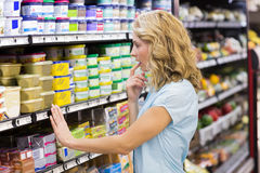 Femme assez blonde regardant des étagères Photos stock