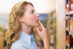 Femme assez blonde regardant des étagères Photographie stock libre de droits