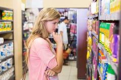 Femme assez blonde regardant l'étagère et la pensée Photos libres de droits