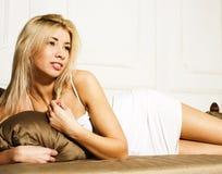 Femme assez blonde s'étendant dans le lit, lingerie sensuelle Photo stock