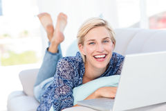 Femme assez blonde se trouvant sur le divan et à l'aide de son ordinateur portable Image libre de droits