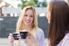 Femme assez blonde souriant à l'appareil-photo et tenant une tasse de café Images libres de droits