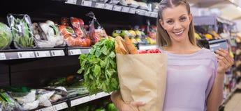 Femme assez blonde tenant le sac et la carte de crédit Photo stock