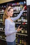 Femme assez blonde tenant une bouteille de vin rouge Photo libre de droits