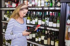 Femme assez blonde tenant une bouteille de vin rouge Photographie stock