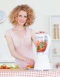 Femme assez blonde utilisant un mélangeur dans la cuisine photographie stock libre de droits