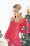 Femme assez enceinte caressant son ventre tout en se tenant images libres de droits