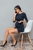 Femme assez enceinte d'affaires parlant par le téléphone Photographie stock libre de droits