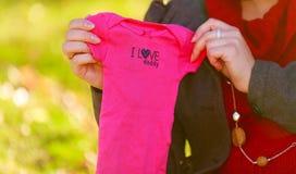 Femme assez enceinte dans la pose rouge en parc vert Jeune femme 15 Photo stock